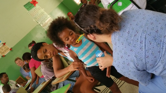Ivy Tech Northeast nursing student Cordelia Turpchinoff applies her child development skills to entertain a young girl as she and her mother await their turn to be seen by a doctor in San Janoa de Azua.
