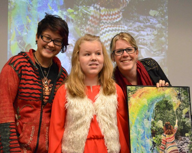 Ivy Tech Northeast visual communications major Colene Smart joins Hannah Hubley, 13, and her mother, Rebekah Hubley, for a class presentation. Smart worked with the Hubleys on an art project that put Hannah, who is blind, into a fantasy setting based on Hannah's interests. Smart's finished piece graces the cover of this issue.