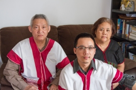 Shwe pictured with his parents in traditional Karen shirts. Karen is one of the seven major cultural groups in Burma. The red represents boldness; the white represents purity.