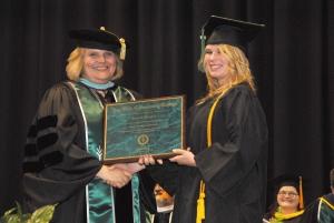 Ivy Tech Northeast Chancellor Jerrilee K. Mosier, Ed. D., presents an award plaque to respiratory care graduate Karrah Hughes.