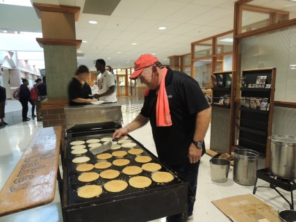 Trevor Muir of Chris Cakes works on his 4-foot grill to serve breakfast to students at Coliseum Campus on Thursday.