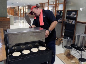 Trevor Muir, of Chris Cakes, uses a machine with four spouts to dispense batter onto the grill.