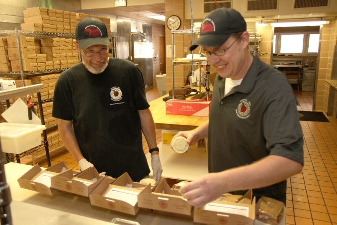 Apple Spice Junction employee Paul Hazelton (left) observes general manager Nate Getts as he packages gourmet boxed lunches. Apple Spice Junction is an affirmative business that employs Park Center clients who have recovered from major mental illness and been out of the workforce for an extended period of time. Following six months of job training from Getts, Hazelton will seek a long-term employment opportunity elsewhere in the community.