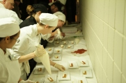 Hospitality administration students add the finishing touch to one of the evening's desserts.