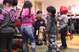 Firefighter Taylor Fitzgerald speaks to the preschoolers about fire rescue protocol before putting on his protective fire gear.