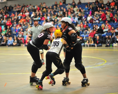 Salyers, at left, plays a blocker with the Fort Wayne Derby Girls. Blockers try to prevent the other team's jammer from scoring. Jammers are denoted by the star on their helmet, seen on the middle skater.