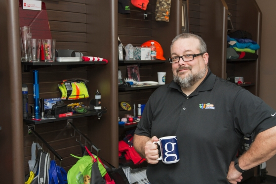 Davis invites local clients looking for customizable promotional items to visit his employer's showroom at YourPromoPeople.com. Some of Davis' most notable work involves swag for country music stars, including the Garth Brooks mug he's holding—a design that required personal approval from Brooks.