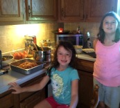 "Maddison, 7, and Vanessa, 9, make dinner. ""I put them to work,"" Lowry says. ""They did a good job. They have their little aprons. It's so cute."""