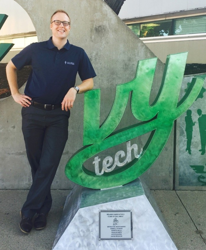 """Andrew Bourne, Assistant Director of Early College Programming & Coordinator of the Ivy Career Advancement Program with """"I in Ivy"""" sculpture near Student Life Center entrance. Sculpture was made by the fall welding fabrication II class, 2015."""