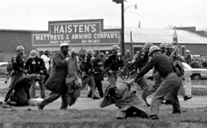 Alabama state troopers swing billy clubs to break up a civil rights voting march in Selma, Ala., on March 7, 1965. In the foreground, John Lewis is struck in the head, for which he is later hospitalized. (Photo courtesy PhotosForClass.com)