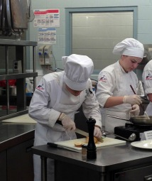 Juanito Gaona and Kelsey Thomas, hospitality administration students, make shrimp scampi.