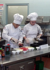 Juanito Gaona and Kelsey Thomas, hospitality administration students, prepare ahi poke, a raw tuna dish with toasted sesame seeds.